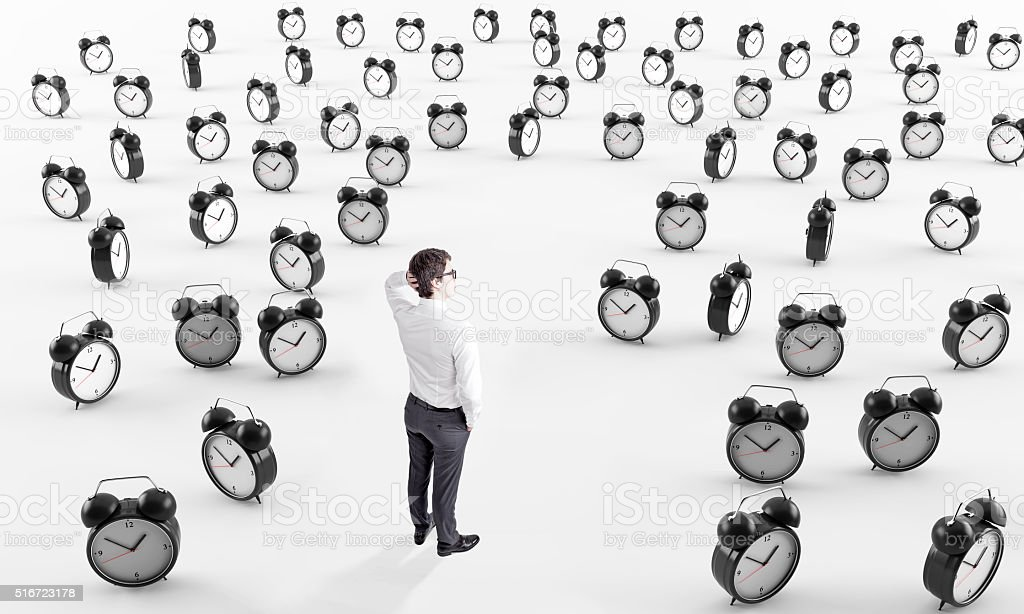 Businessman surrounded by alarm clocks stock photo