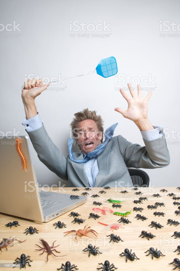 Businessman Swatting Bugs on Desk royalty-free stock photo