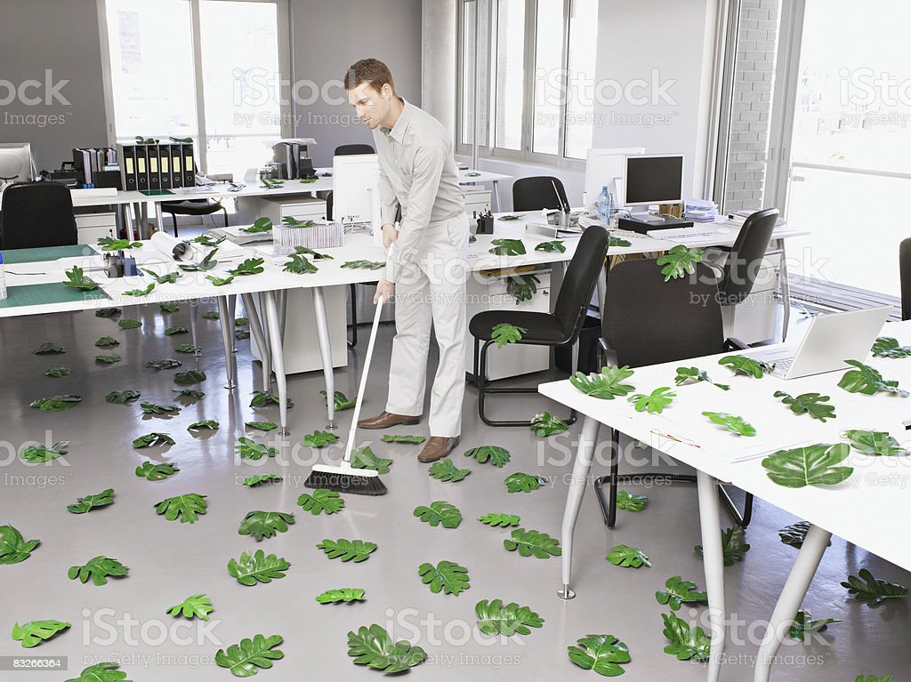 Businessman sweeping up green leaves in office royalty-free stock photo