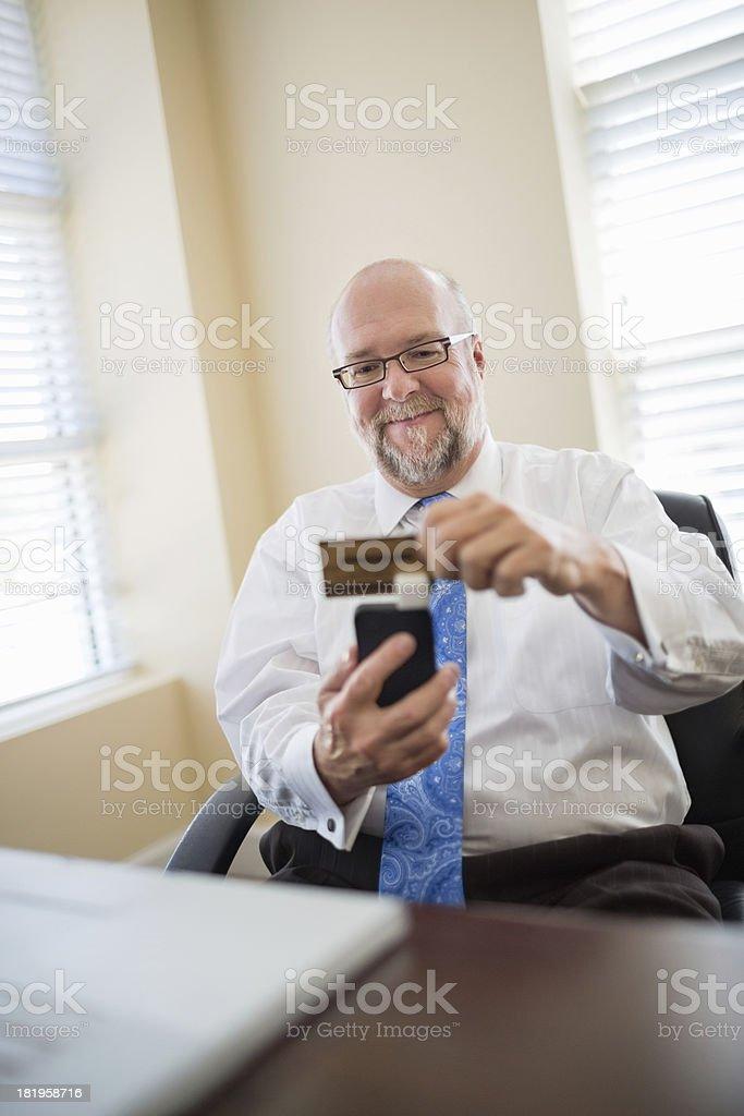 Businessman Swiping Credit Card Using Reader stock photo