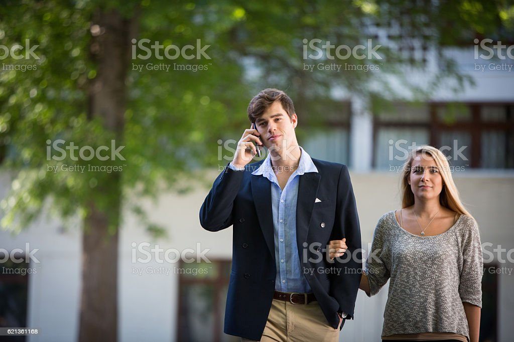 Businessman takes a call while walking with his partner stock photo