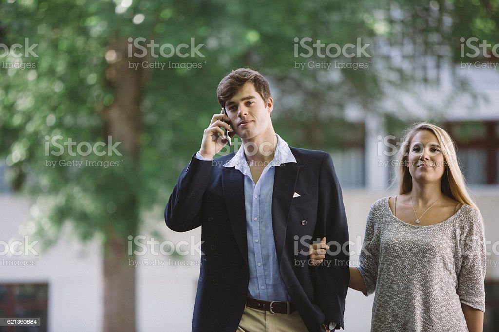 Businessman takes a call while walking with his wife stock photo