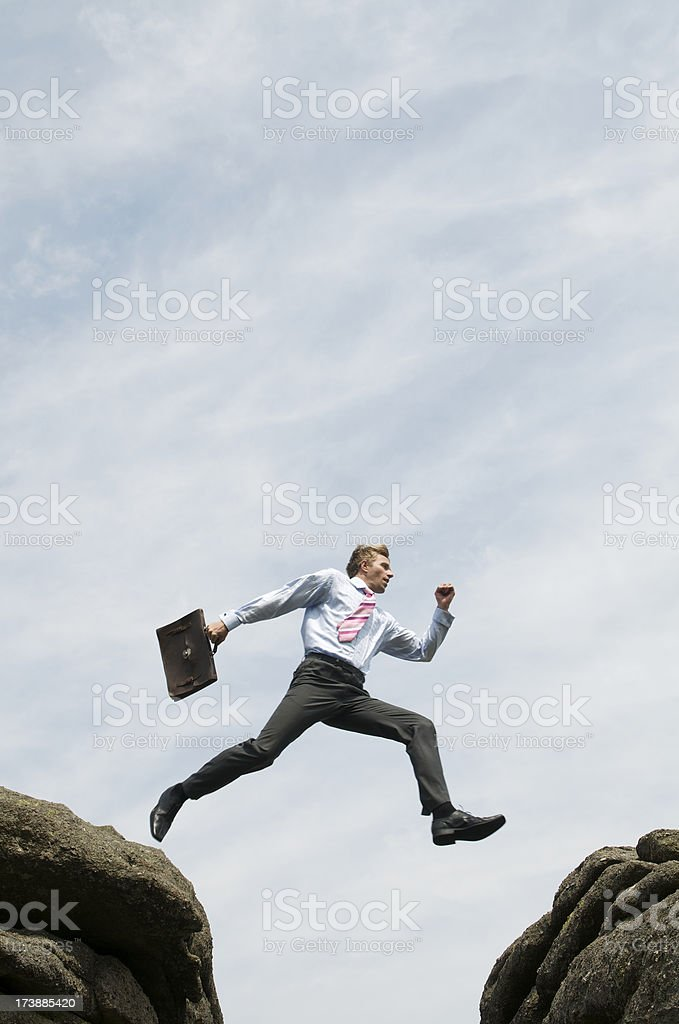 Businessman Takes a Confident Leap Across the Divide royalty-free stock photo