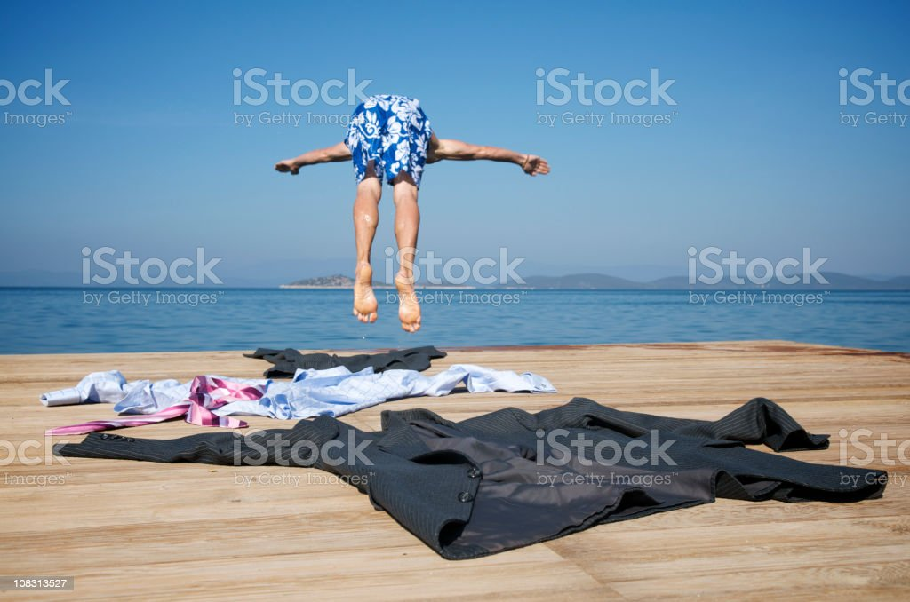 Businessman Takes off Suit and Dives into Sea stock photo