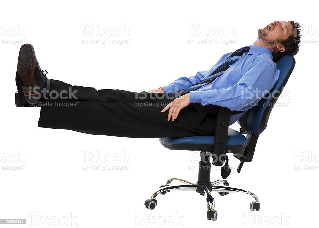 Businessman taking a nap with his feet up in office chair stock photo