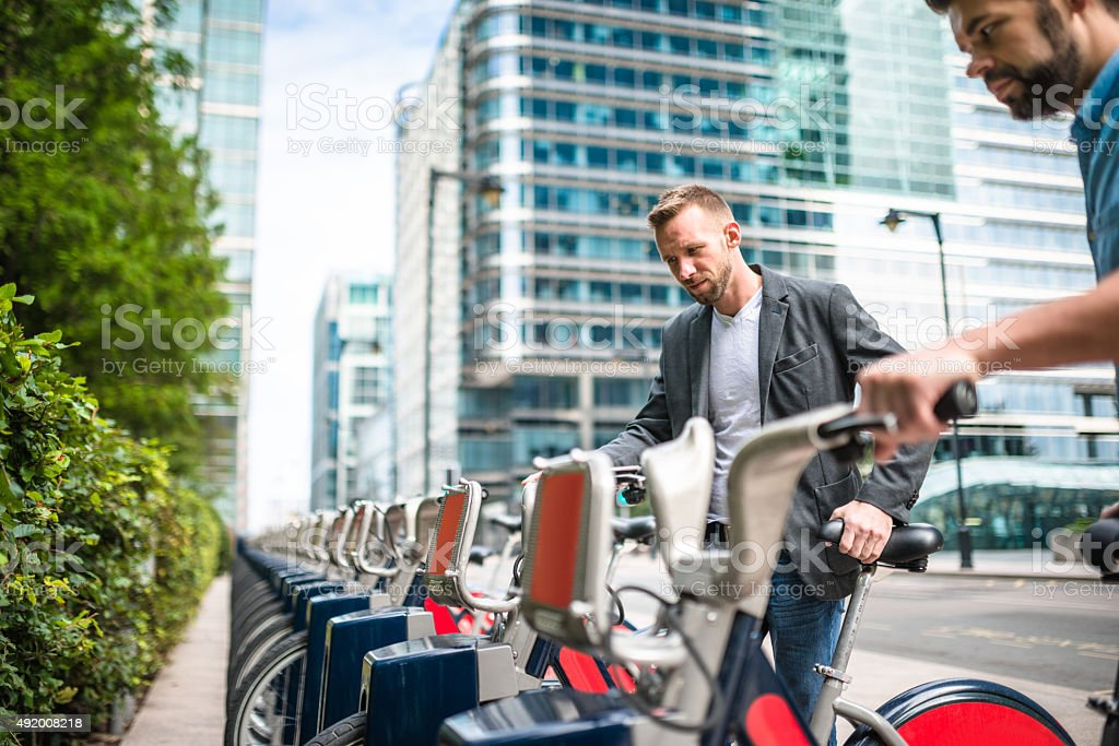 businessman taking a rental bike on the city stock photo