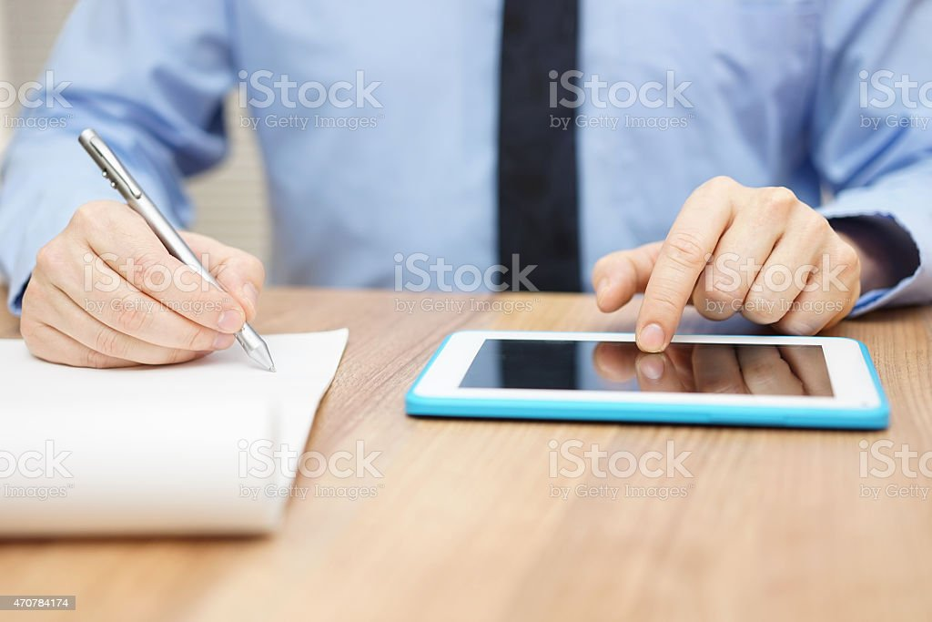 Businessman taking business notes and working on tablet computer stock photo