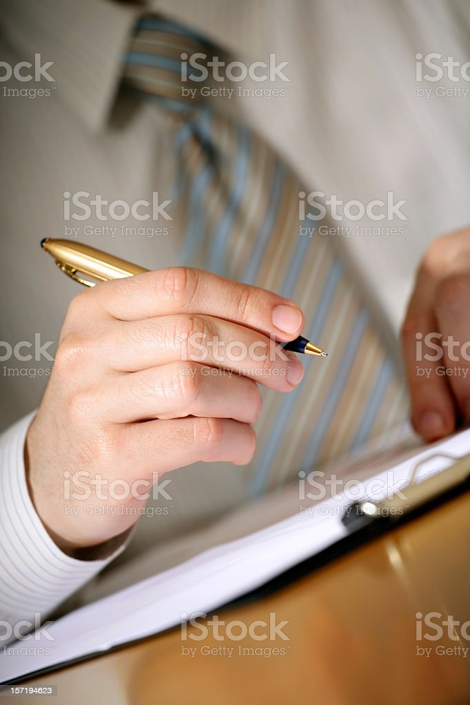 Businessman taking notes with gold pen royalty-free stock photo