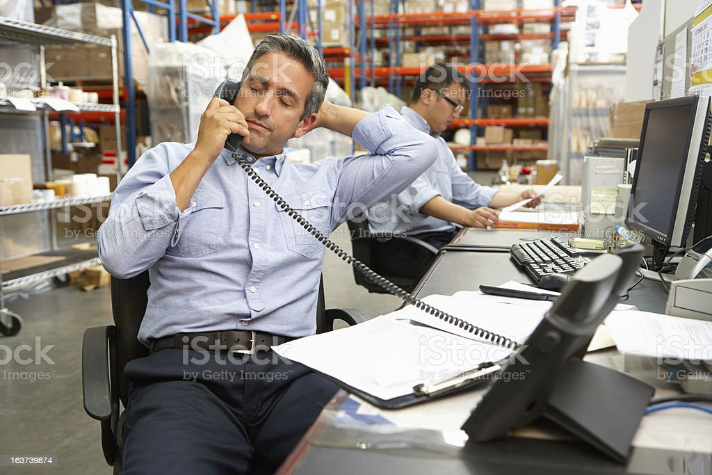 Businessman taking phone call at his warehouse desk royalty-free stock photo