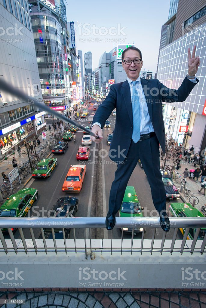 Businessman taking selfie balancing on a handrail. stock photo