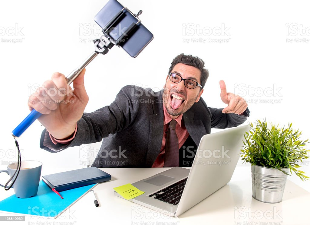 businessman taking selfie photo with mobile phone camera and stick stock photo