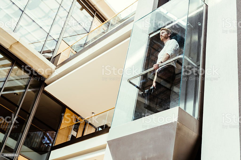 Businessman taking the elevator stock photo