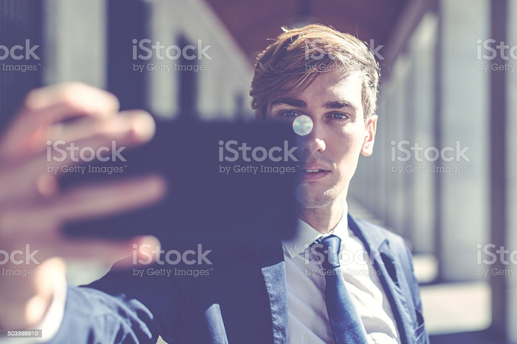 Businessman talking a selfie with mobile phone stock photo