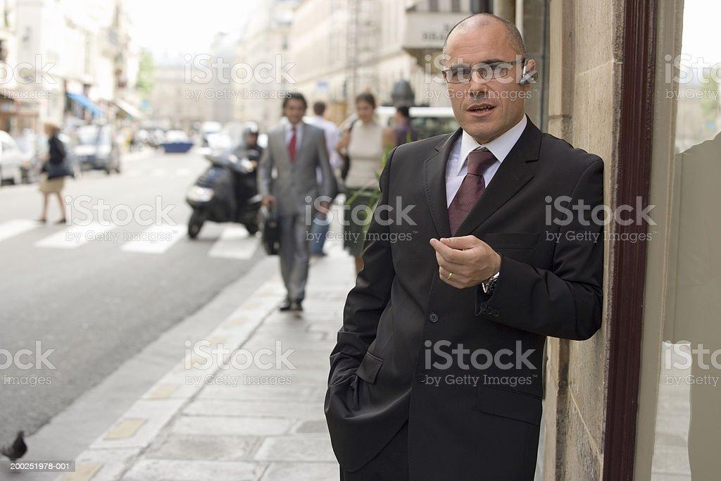 Businessman talking in street wearing mobile phone earpiece royalty-free stock photo