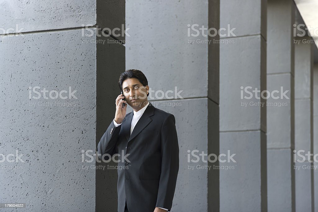 Businessman Talking on Cell Phone Against Gray Building royalty-free stock photo