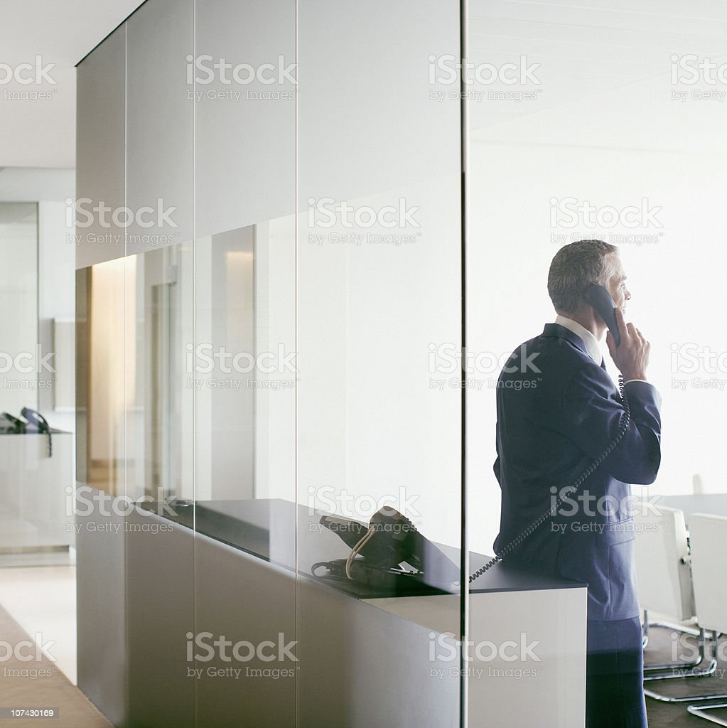Businessman talking on cell phone in conference room stock photo