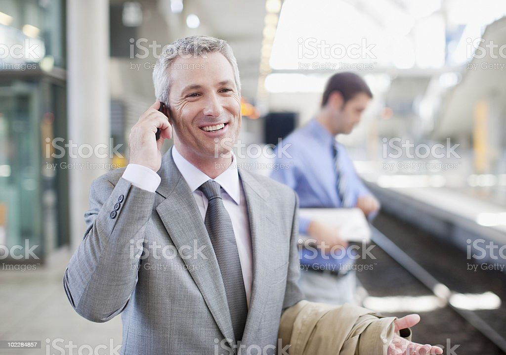 Businessman talking on cell phone on train platform royalty-free stock photo