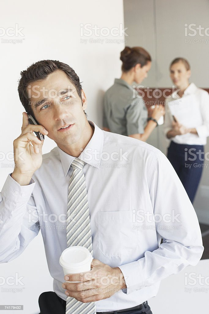 Businessman talking on cell phone with two women in background royalty-free stock photo