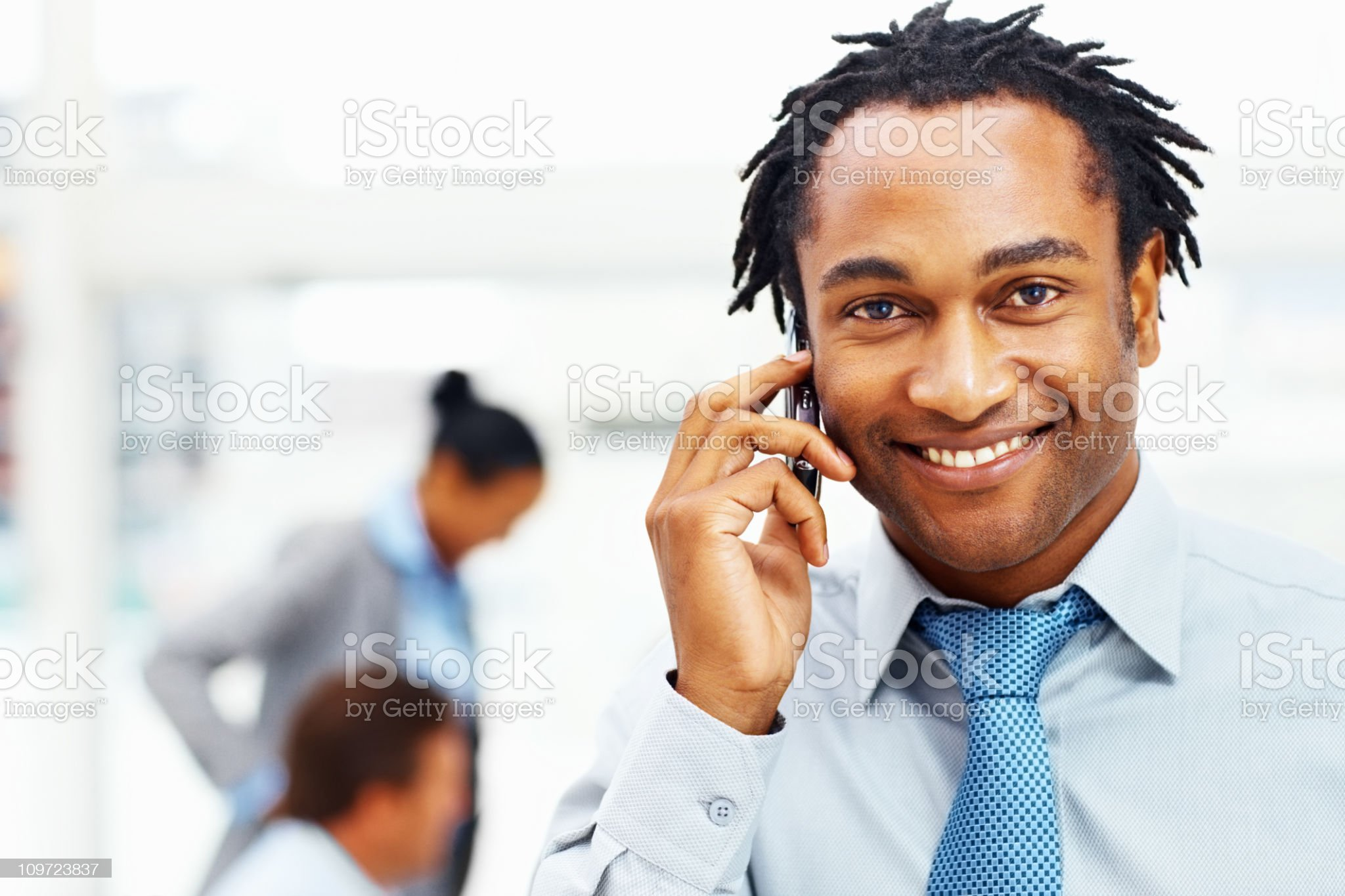Businessman talking on cellphone with colleagues in the background royalty-free stock photo
