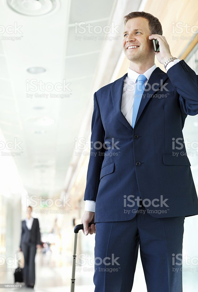 Businessman Talking On His Mobile Phone At The Airport royalty-free stock photo