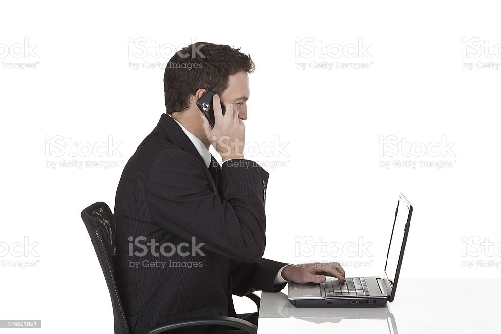 Businessman talking on mobile phone and using a laptop royalty-free stock photo