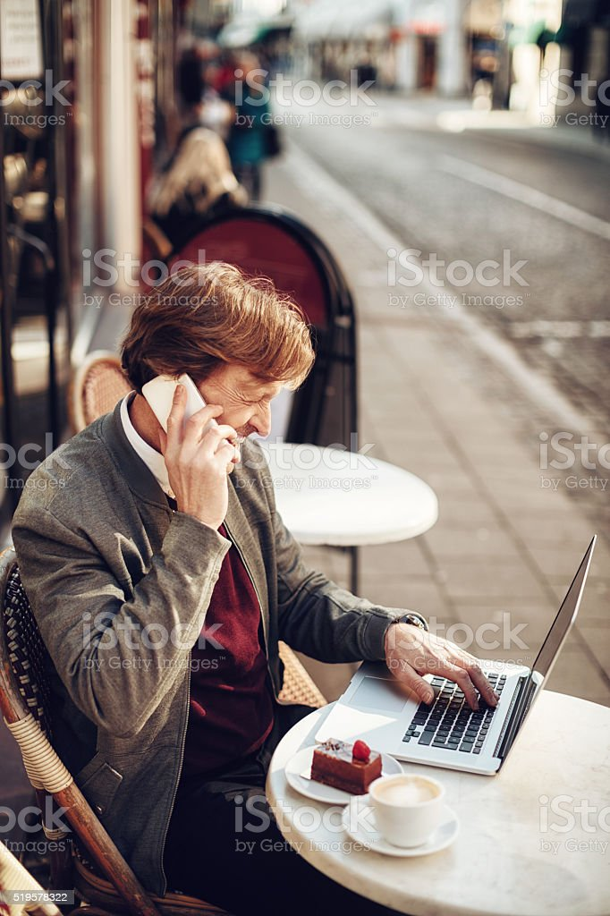 Businessman talking on mobile phone in cafe stock photo