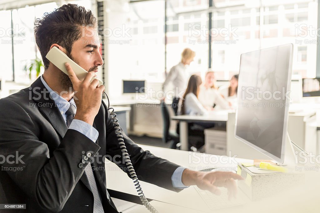 Businessman talking on phone and working in office stock photo