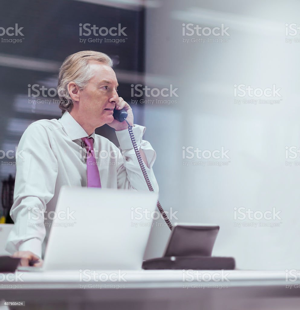 Businessman talking on phone in business office stock photo