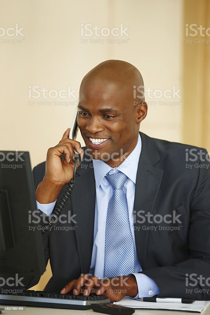 Businessman talking on phone in front of computer royalty-free stock photo