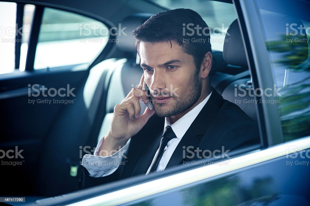 Businessman talking on the phone in car stock photo