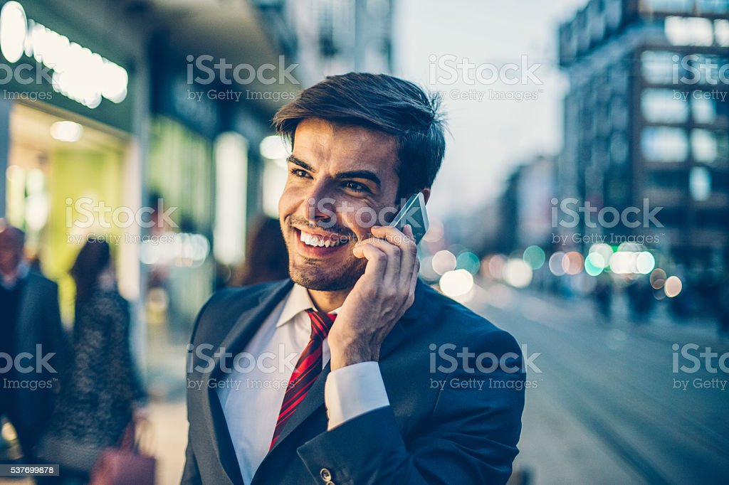 Businessman talking on the phone outdoors in the evening stock photo