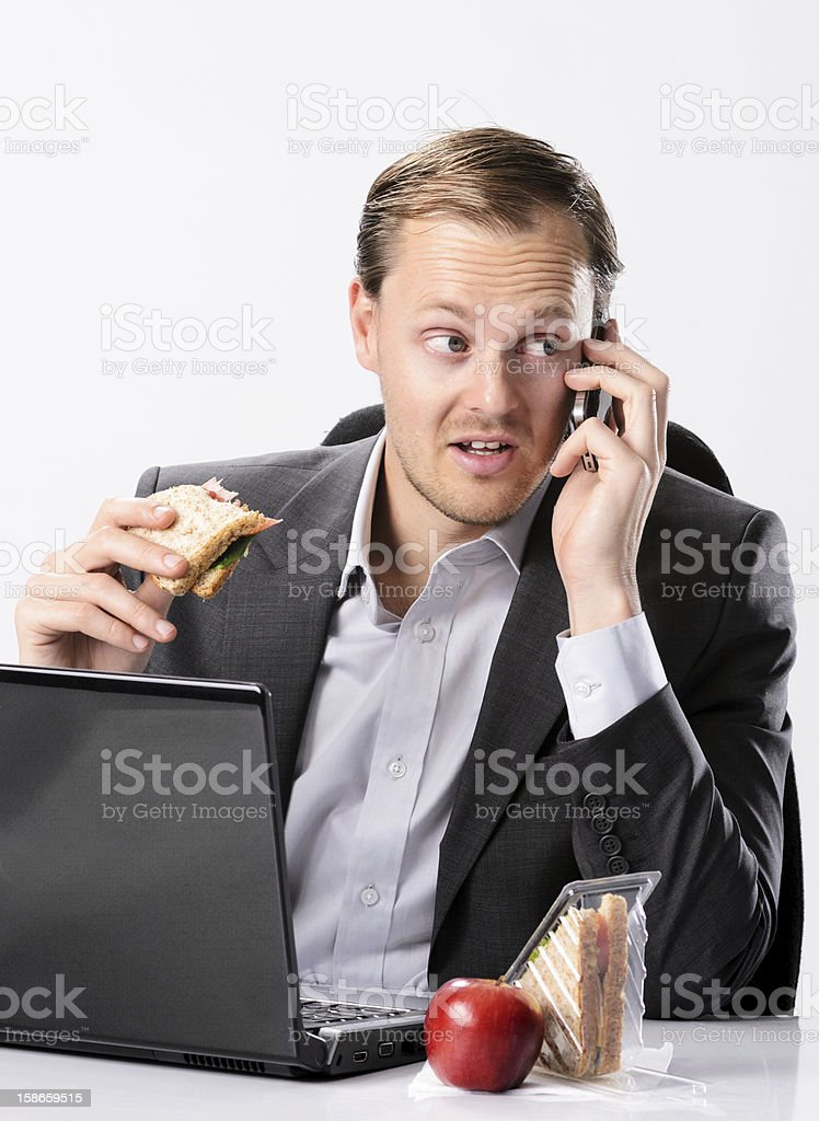 A businessman talking on the phone while eating stock photo