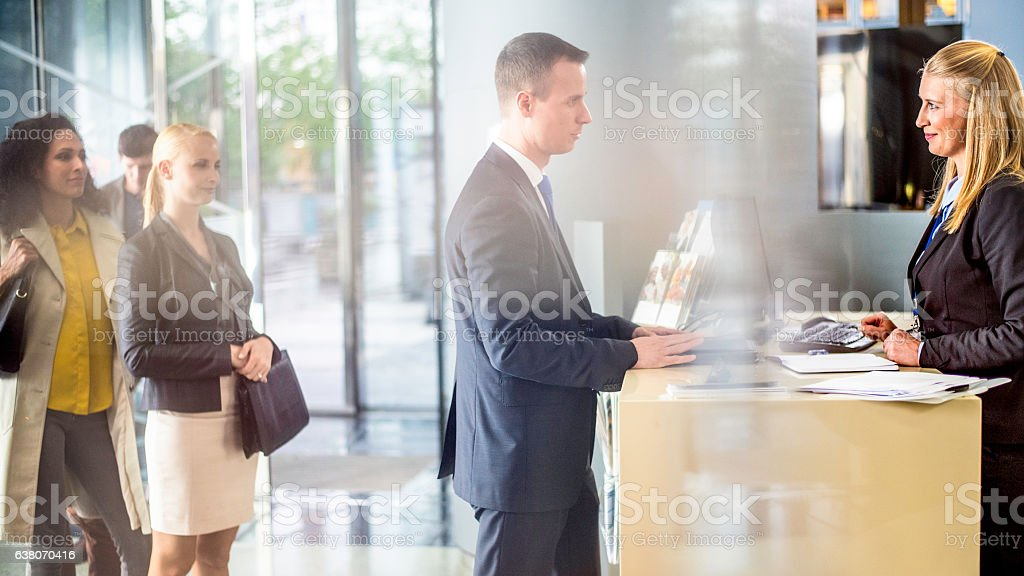 Businessman talking to bank teller at the counter stock photo