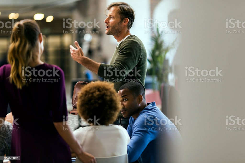 Businessman talking to colleagues in meeting stock photo