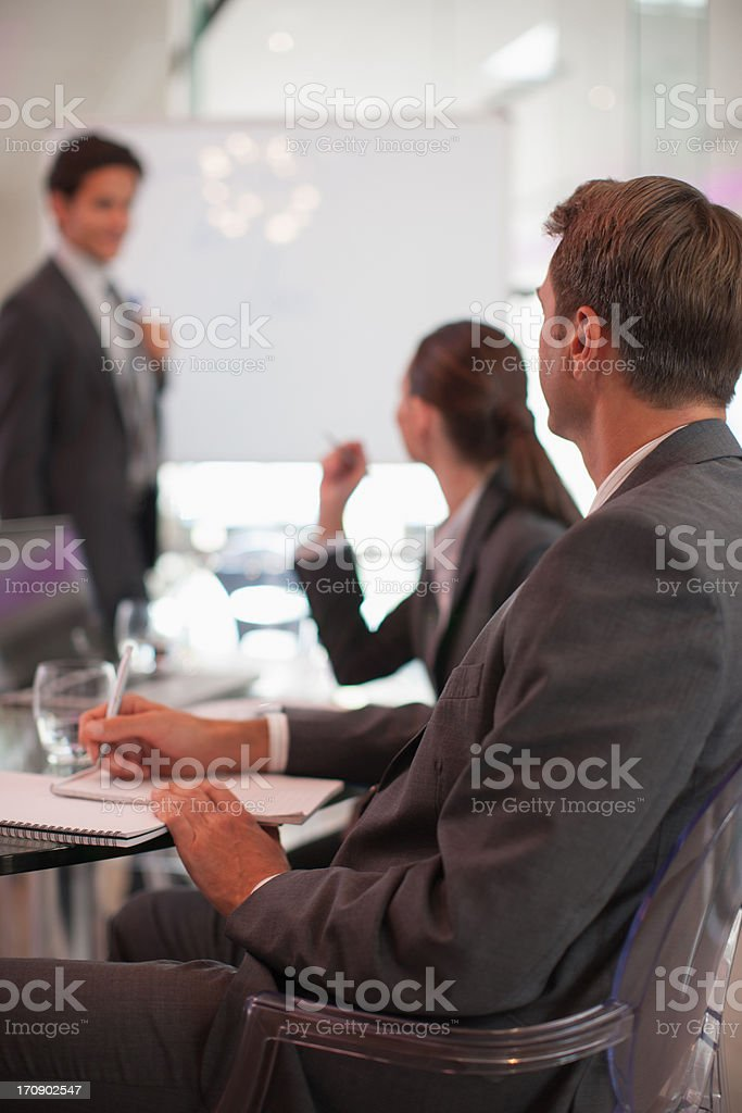 Businessman talking to co-workers in conference room stock photo