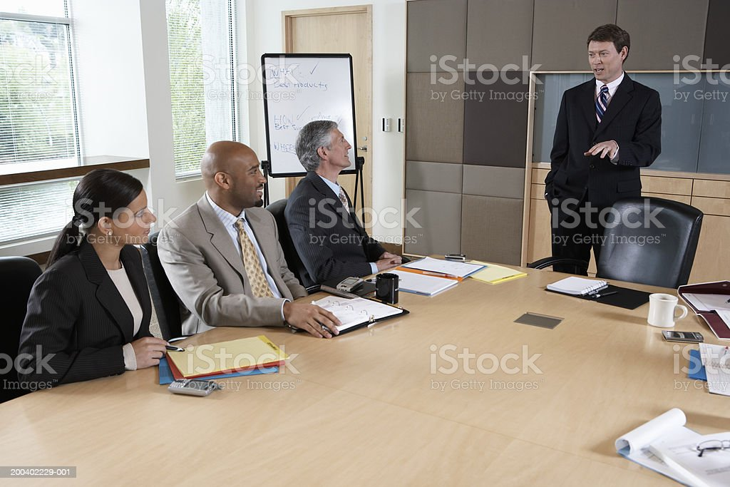 Businessman talking to executives during meeting in boardroom royalty-free stock photo