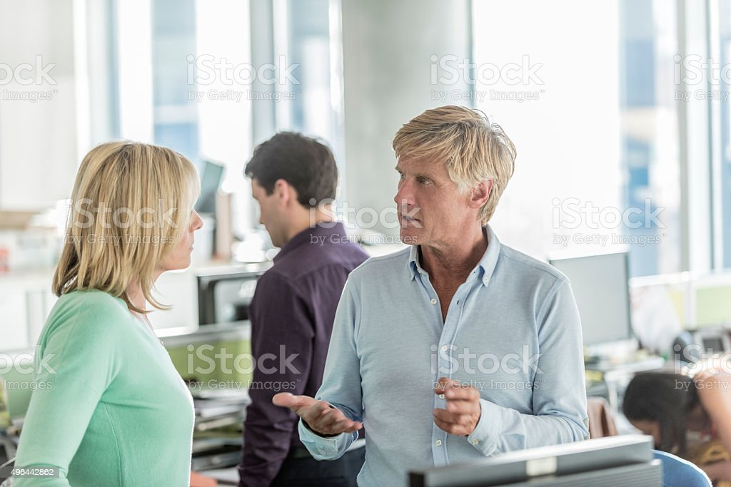 Businessman talking to female colleage in modern office stock photo