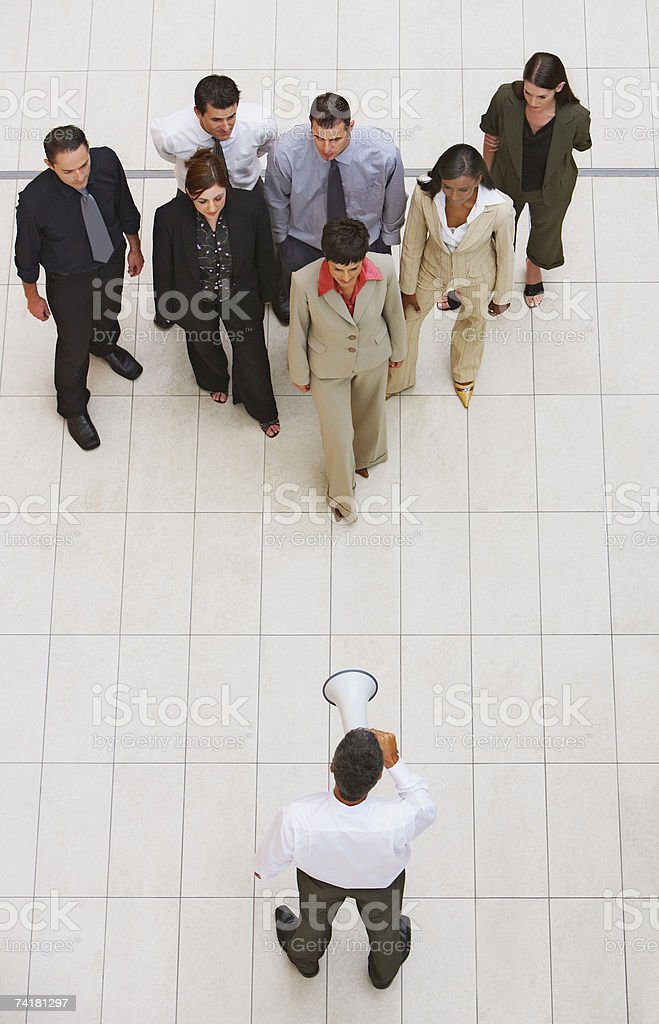 Businessman talking to group of businesspeople with megaphone stock photo