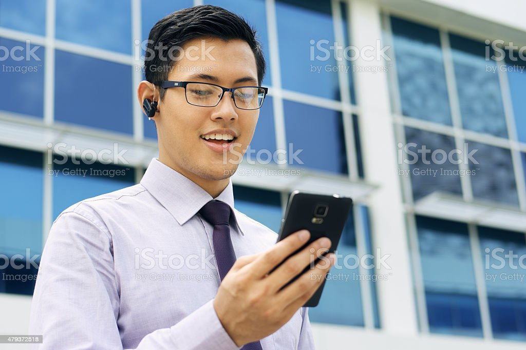 Businessman Talking Video Call On Mobile With Bluetooth Handsfre stock photo