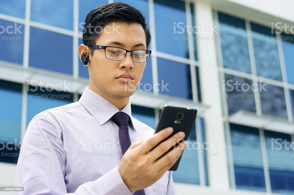 Businessman Talking Video Call On Mobile With Bluetooth Headset stock photo
