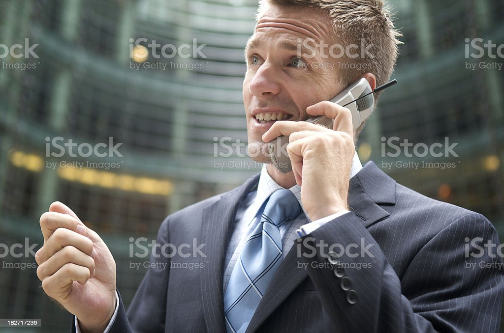 Businessman Talks Outside on Mobile Phone at Office Building stock photo