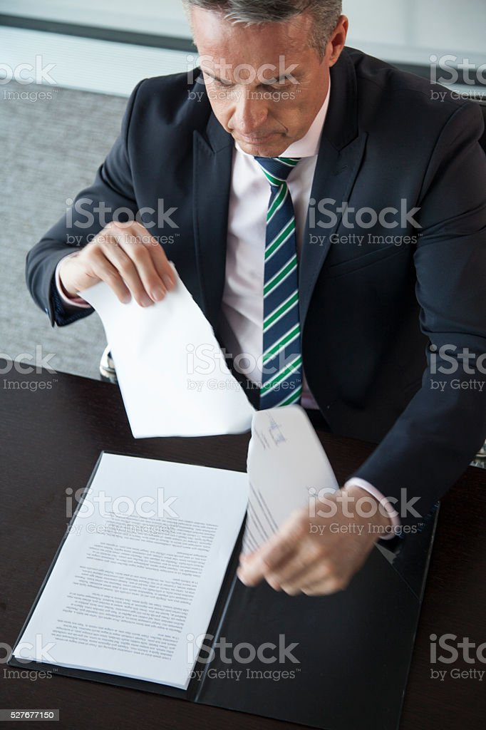 Businessman tearing paper stock photo