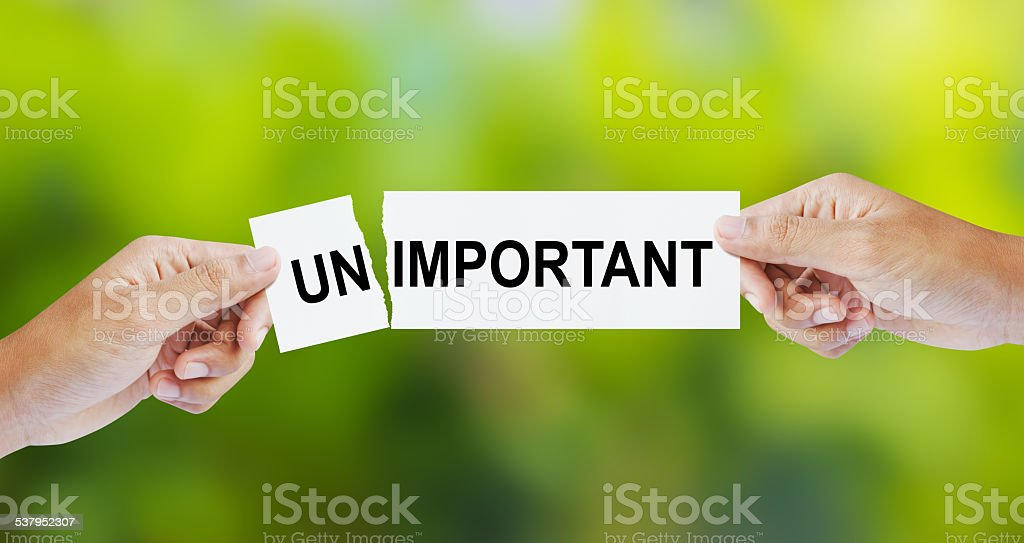Businessman tearing the word Unimportant for Important stock photo