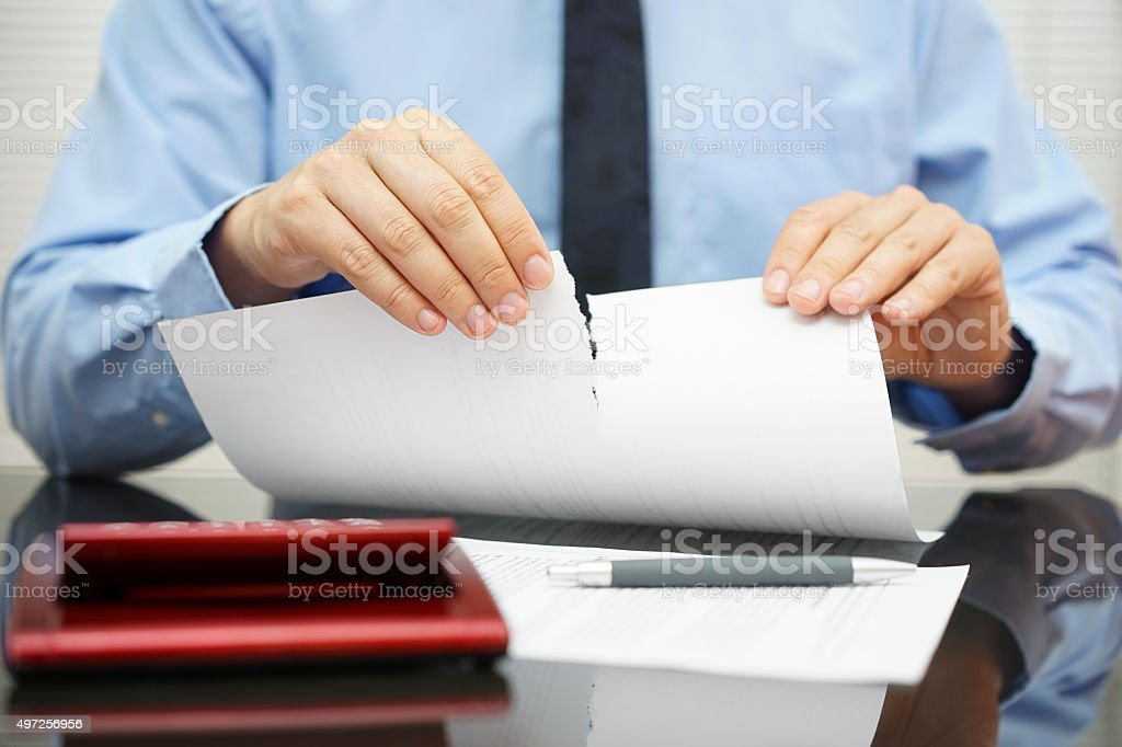 businessman tears document in office stock photo
