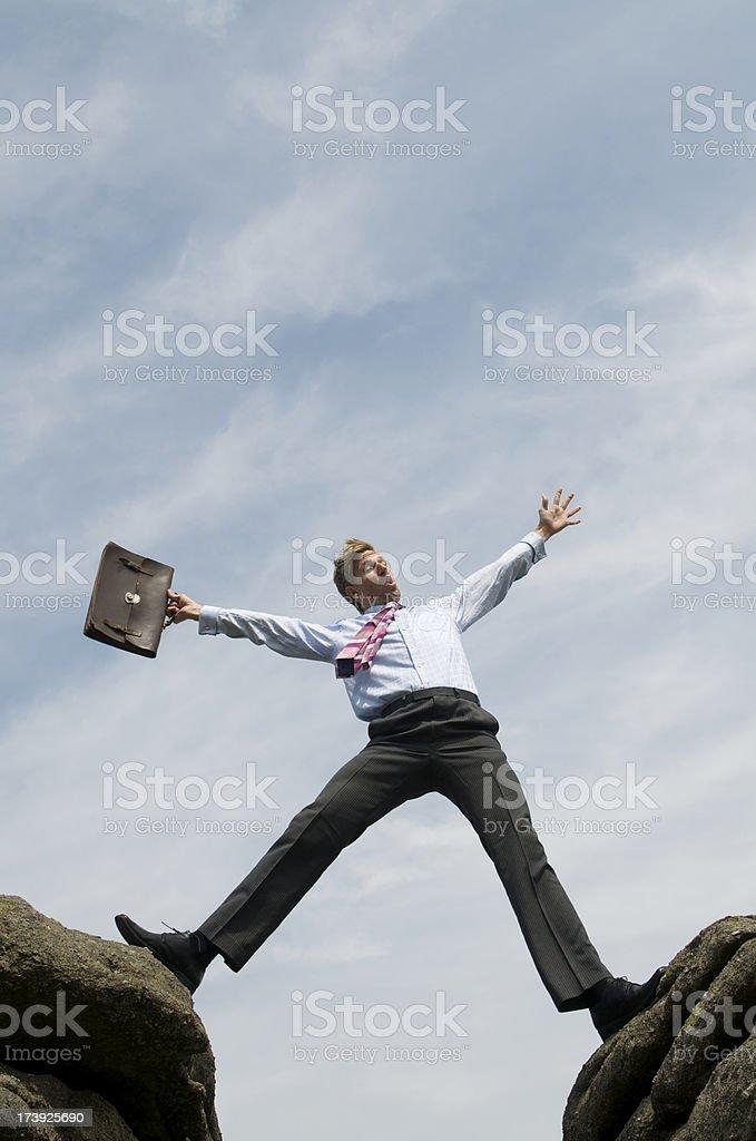 Businessman Teeters above a Steep Ravine royalty-free stock photo