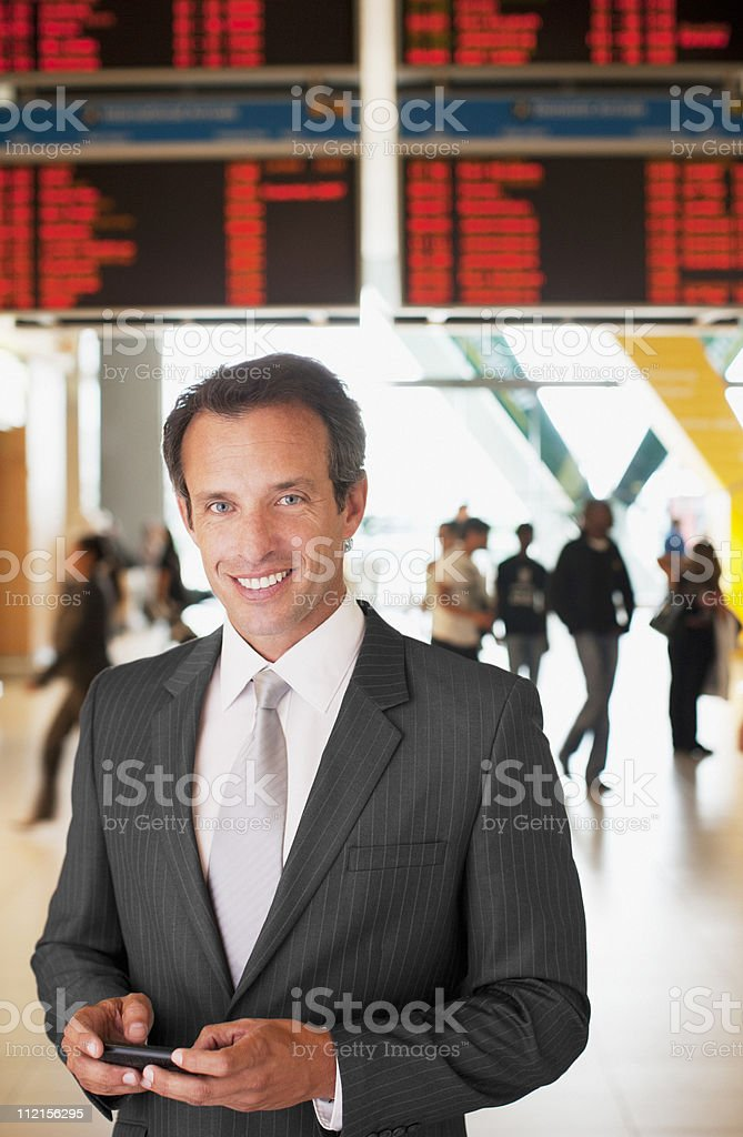 Businessman text messaging on cell phone in airport royalty-free stock photo