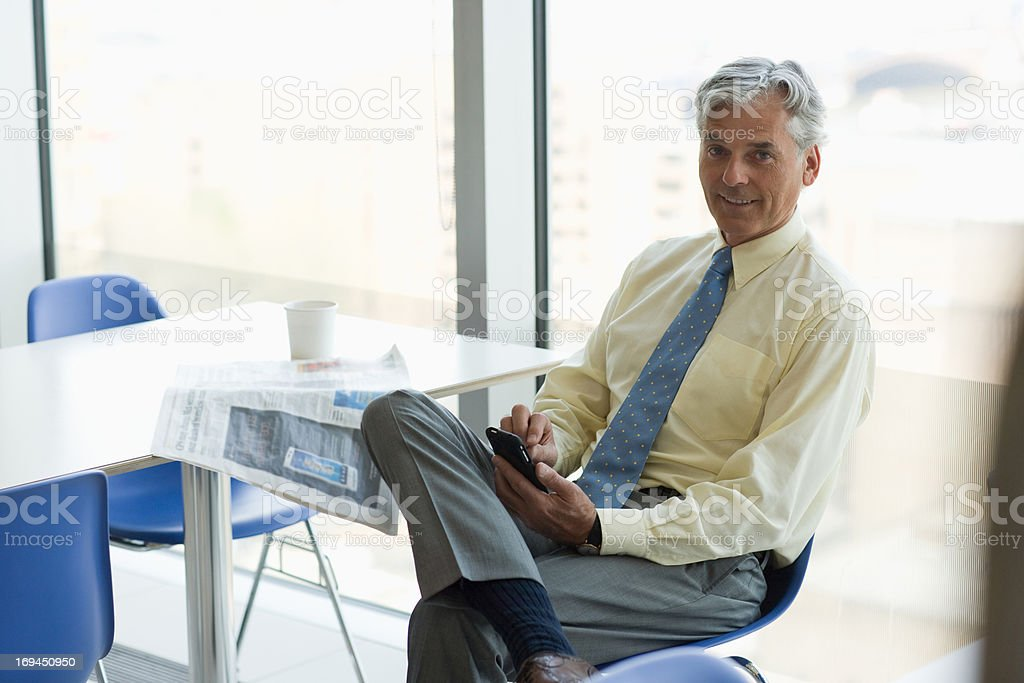 Businessman text messaging on cell phone in cafeteria royalty-free stock photo