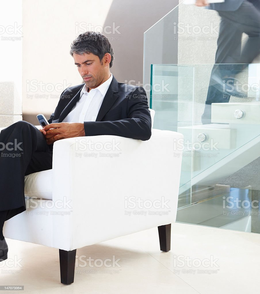 Businessman text messaging on cellphone in an office royalty-free stock photo