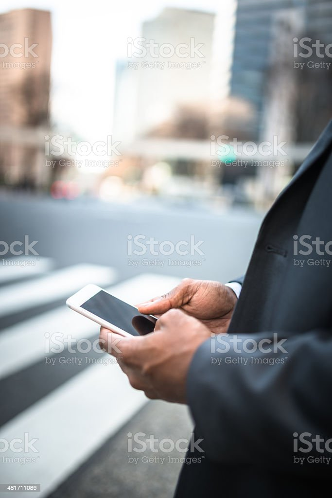 businessman text messaging on the phone in the street stock photo