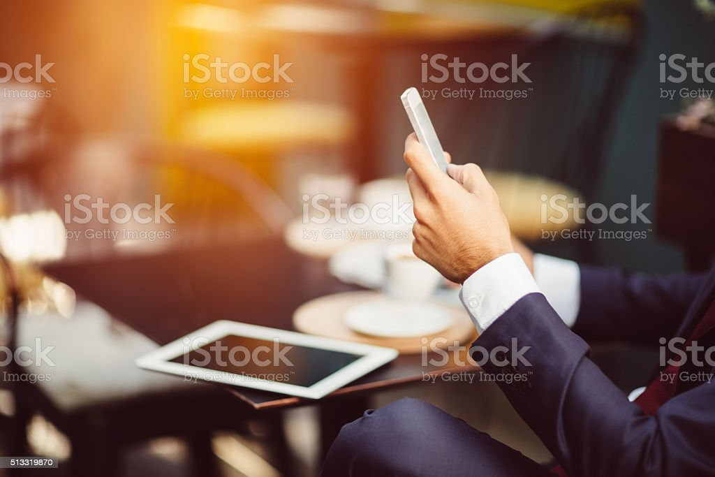 Businessman texting at sidewalk cafe stock photo